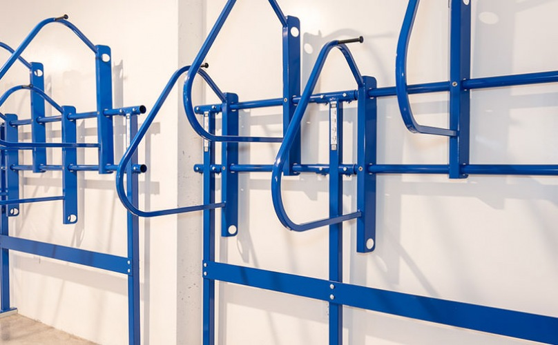 bicycle rack on wall with multiple spaces for storing bikes